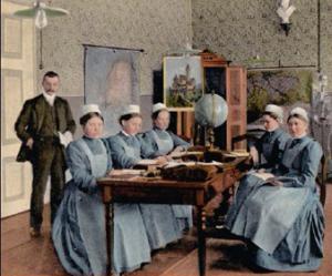 Foto: 5 Frauen mit langem Kleid und Schürze sitzen um einen Tisch und lesen, daneben steht ein Mann in Anzug