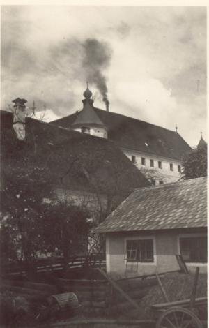 Foto der Tötungsanstalt Hartheim mit rauchendem Schornstein des Krematoriums, 1940/41 - © Wolfgang Schuhmann